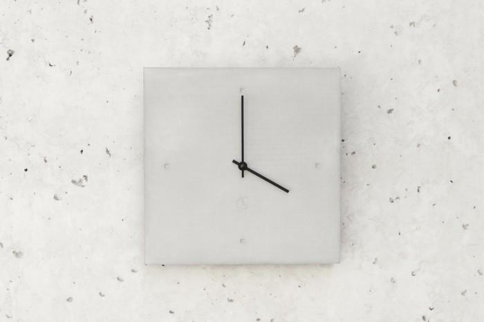 c-clock-no-1-graue-wanduhr-mit-schwarzen-zeigern-auf-beton