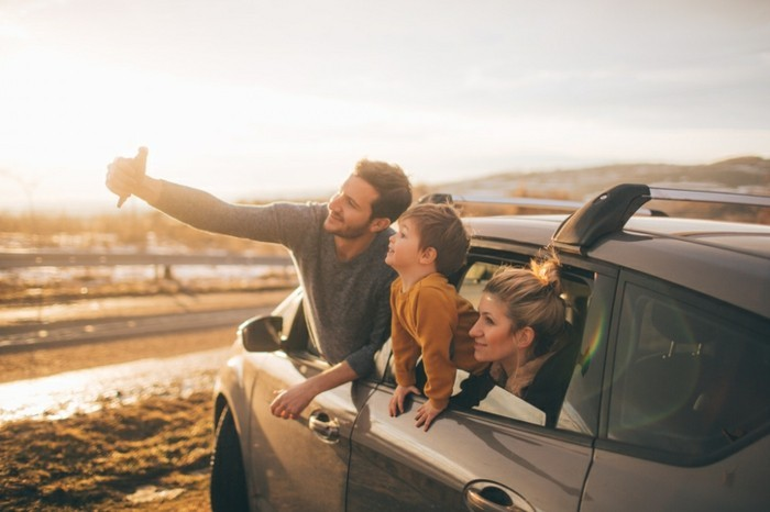 Photo of cute little family posing for the selfie in the nature, during their excursion with family car