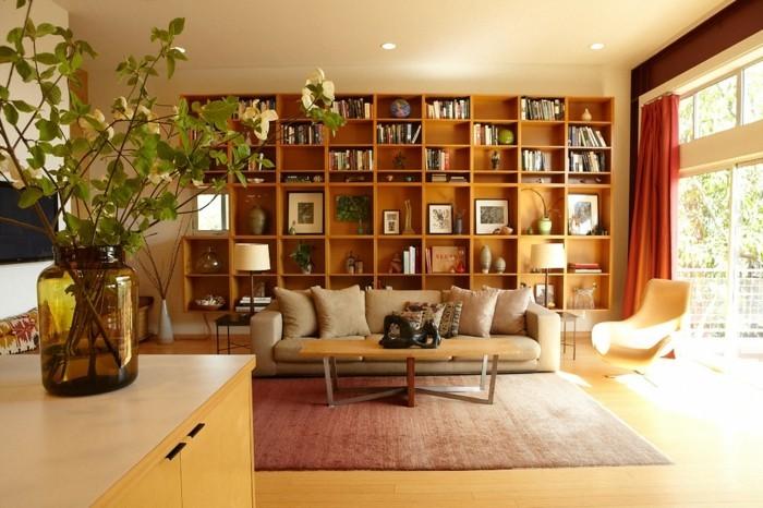 buecherregal-wohnzimmer-aus-hellem-holz-hinter-beige-sofa