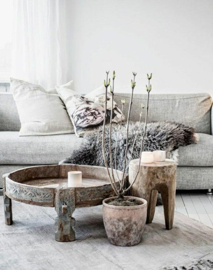 couchtisch-massivholz-rund-tischdeko-kerzen-holzhocker-pflanze-teppich-holboden-graue-couch-mit-kissen