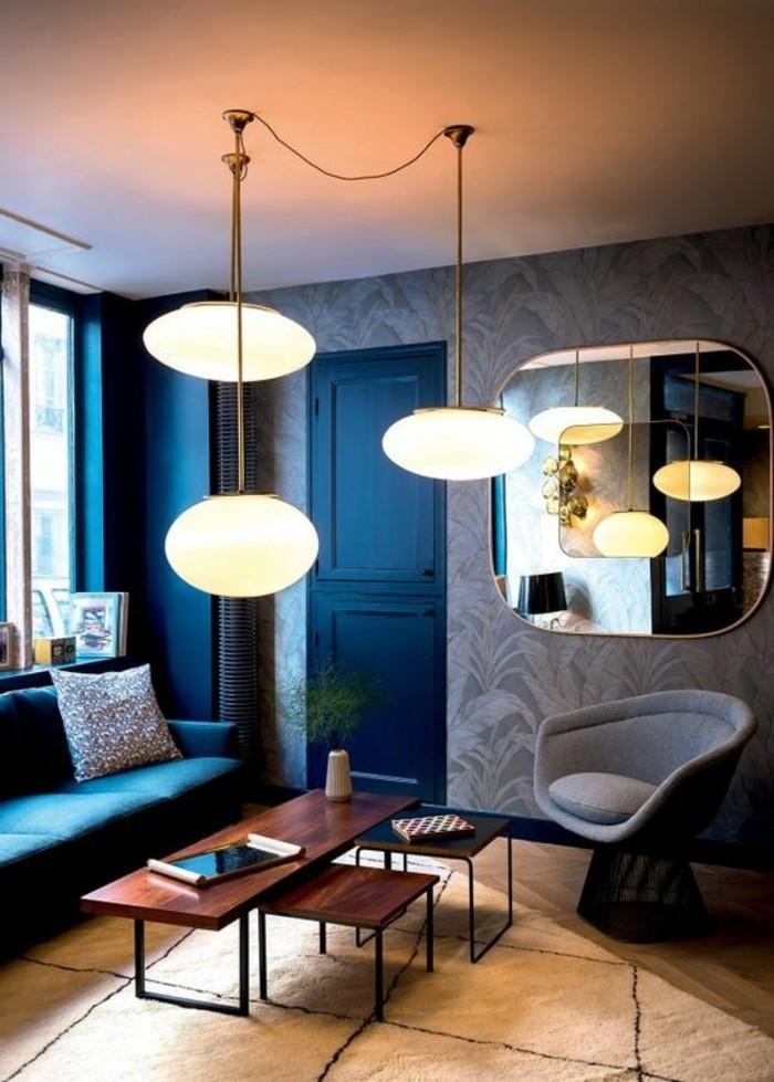 couchtisch-nussbaum-tisch-set-drei-tische-viereckig-dunkles-wohnzimmer-blaue-waende-weisser-plueschteppich-spiegel-indirektes-licht