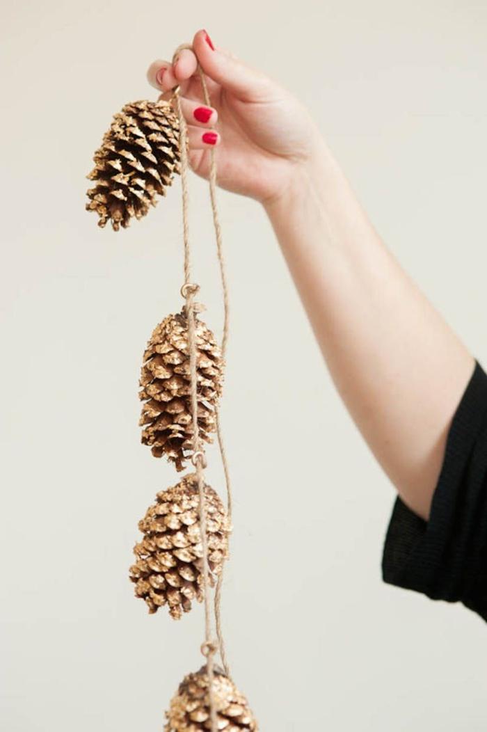 dekoration mit zapfen weihnachten basteln winter inspiration hand hält tannenzapfen girlande weihnachtsdekoration