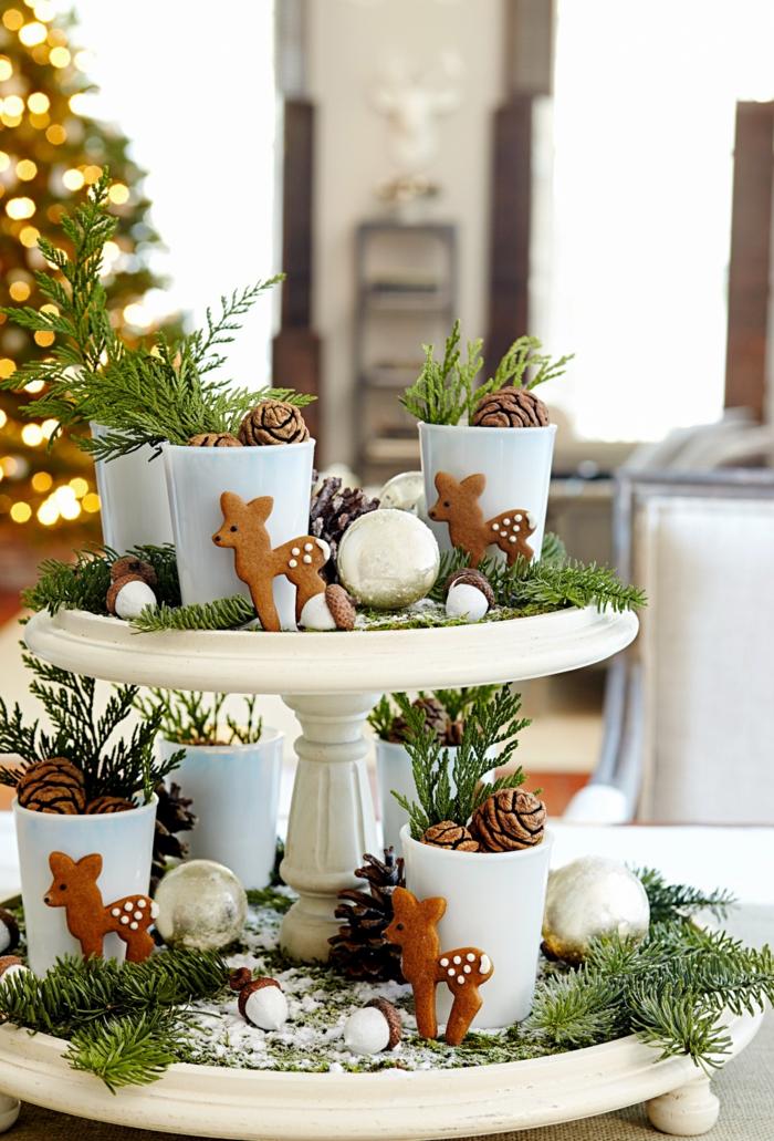 dekorierter kuchenständer rehfiguren tannenzweigen schnee tischdeko weihnachten inspiration weihnachtsdeko basteln