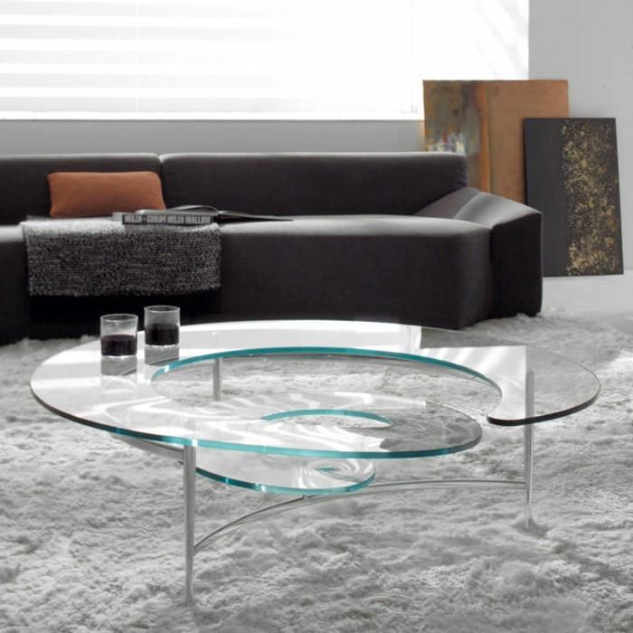 designer-couchtische-glas-rund-weisser-plueschteppich-dunkle-couch-orange-kisse