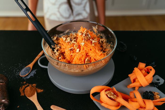 Geriebene Karotten und gehackte Walnüsse in den Teig geben, Teig für Karottenkuchen
