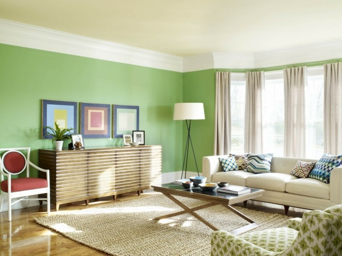 farbgestaltung-wohnzimmer-gruene-waende-lange-gardinen-in-beide-weisser-couch-gruener-sessel-teppich-holzboden-stehlampe-holztisch-pflanze-roter-stuhl