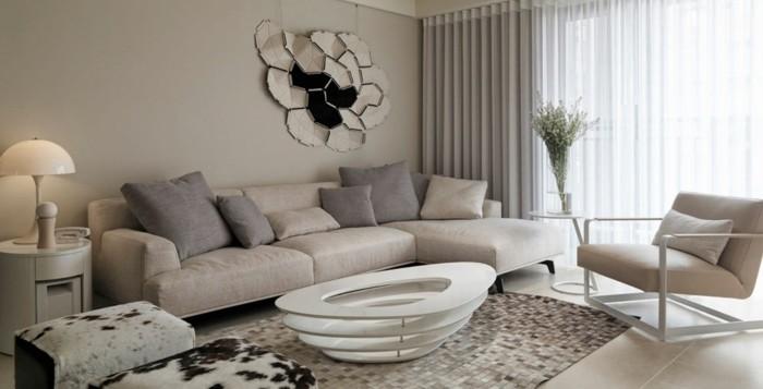 futuristischer-couchtisch-weiss-ovale-form-beige-einrichtung-lederstuhl-wanddeko-blumen