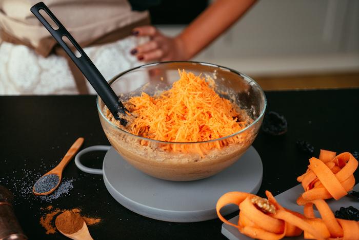 Geriebene Karotten in den Teig geben, Rezept für glutenfreien Karottenkuchen