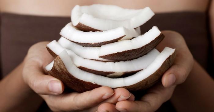 haarkur-selbstgemacht-natuerliches-mittel-aus-kokos-auf-scheiben-in-haenden-einer-frau