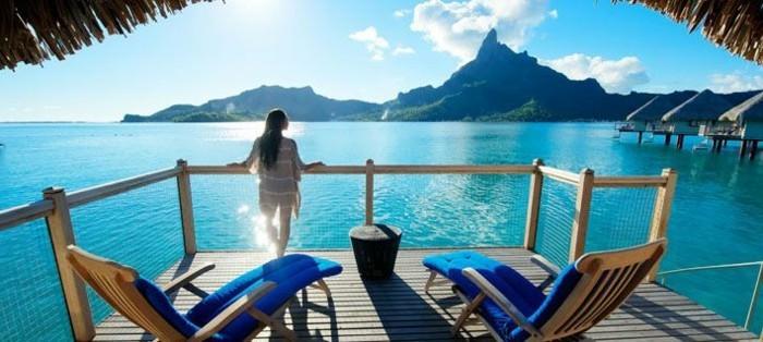 insel-bora-bora-atoll-aussicht-geniessen-eine-frau-steht-auf-der-terrasse-und-trinkt-den-morgenkaffee