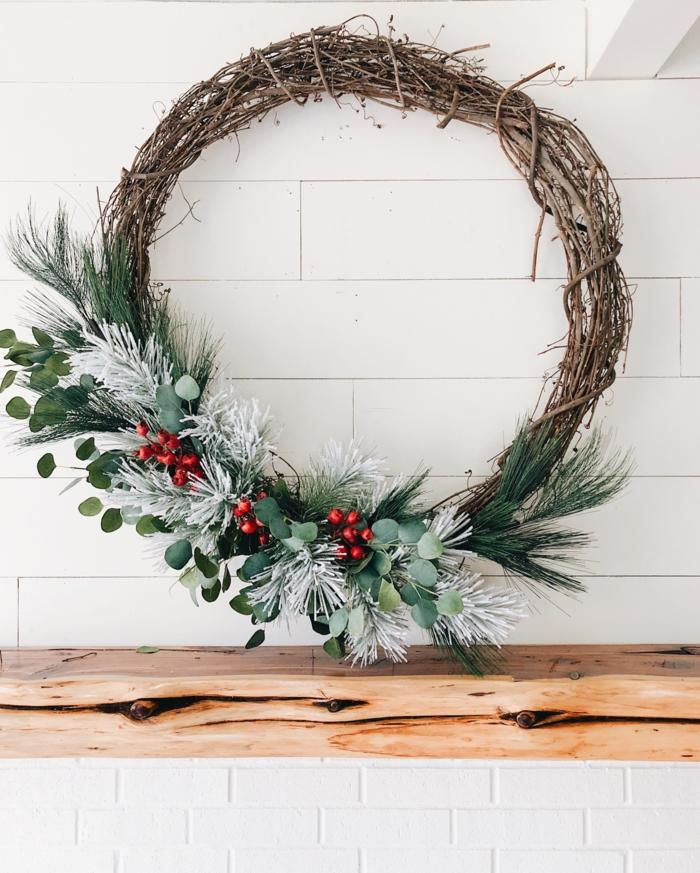 kranz aus baumzweigen dekoriert mit tannenzweigen und roten blüten weihnachtsbastelideen kreativ