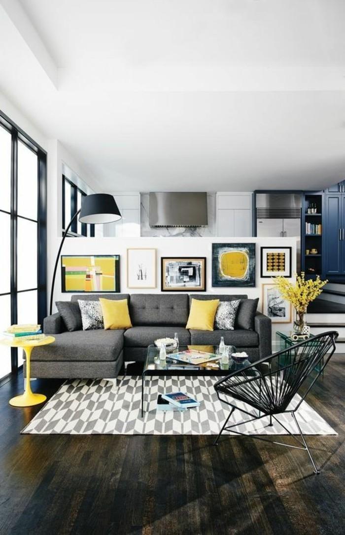 moderne-wandgestaltung-mit-vielen-bildern-grauer-sofa-gelber-stuhl-tisch-aus-glas