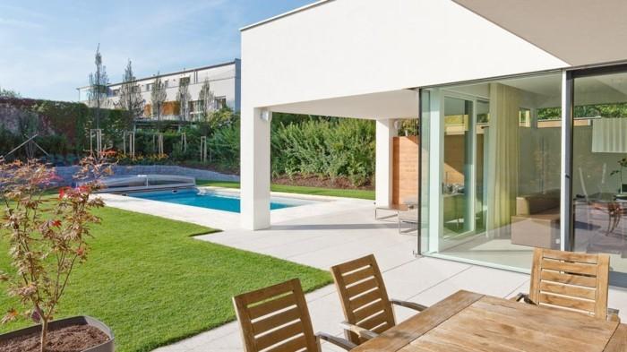 modernes-haus-weisse-terrassenfliesen-schwimmenbad-tisch-aus-holz