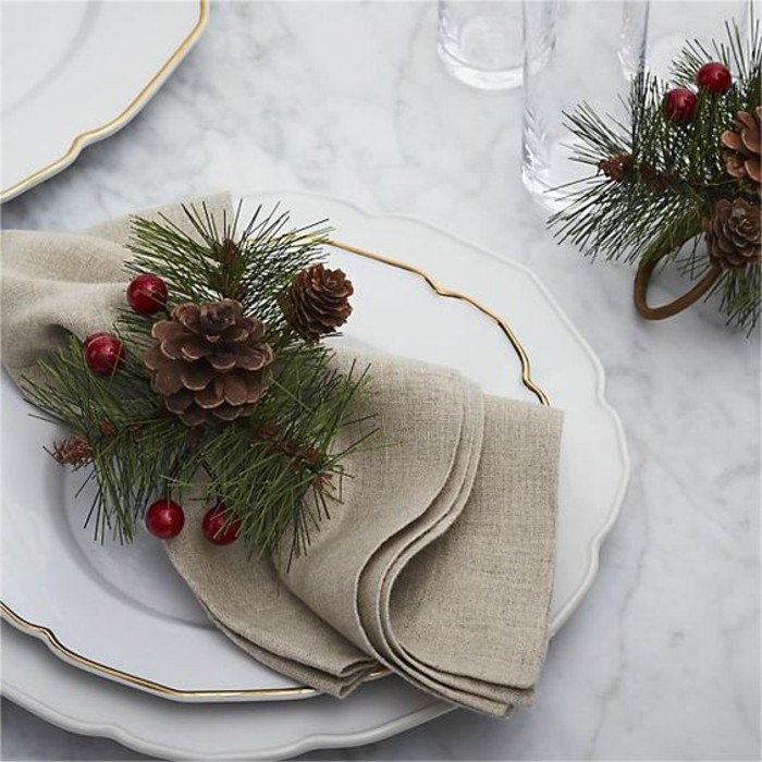 servietten-falten-weihnachten-grune-zweigen-tannenzapfen-vogelbeeren-weise-teller-mit-goldenen-eklementen