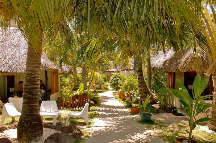 hotel mit privatem strand auf insel bora bora schöne grüne pflanzen palmen alee liegestühle häuschen