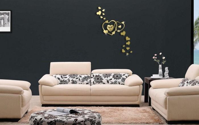 wanduhr-xxl-form-herz-zifferblatt-gold-schwarze-wand-beige-einrichtung-leder-hocker-pflanzenmotive