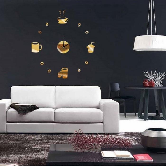 wanduhr-xxl-gold-kaffeetasse-weisse-couch-schwarze-wand-schwarzer-stuhl-schwarzer-tisch-indirektes-licht