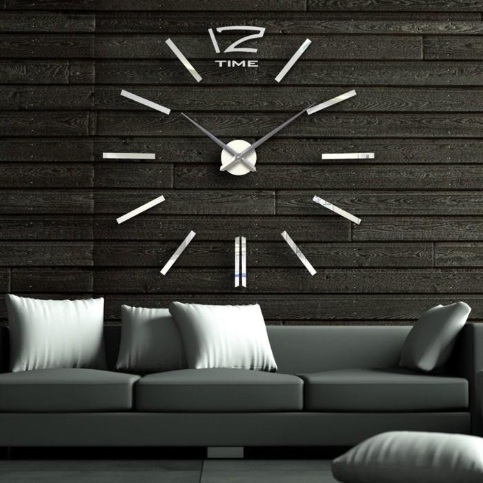 wanduhr-xxl-metallzifferblatt-holzwand-wandverkleidung-dunkelgraue-couch-weisse-kissen