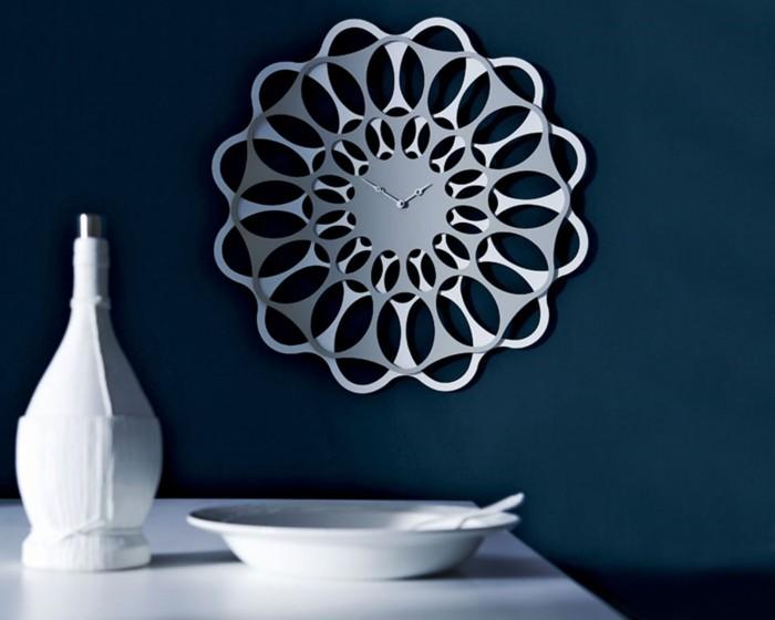 wanduhren-modern-metall-form-pflanze-wanddeko-fuer-dunkelblaue-wand-weisser-tisch