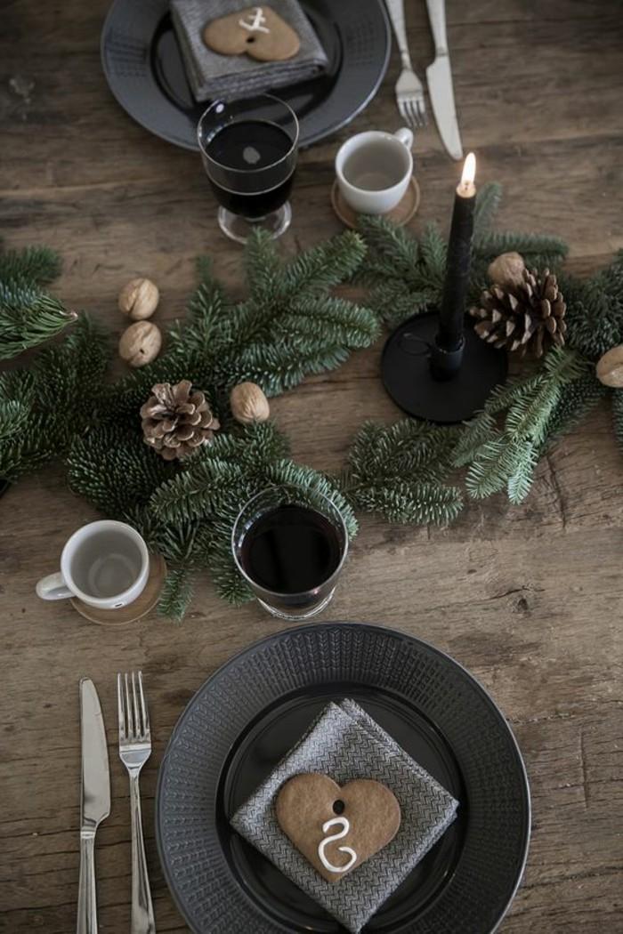 weihnachtliche-tischdeko-in-schwary-und-grau-mit-immergrunen-zweigen-und-tannenzapfen