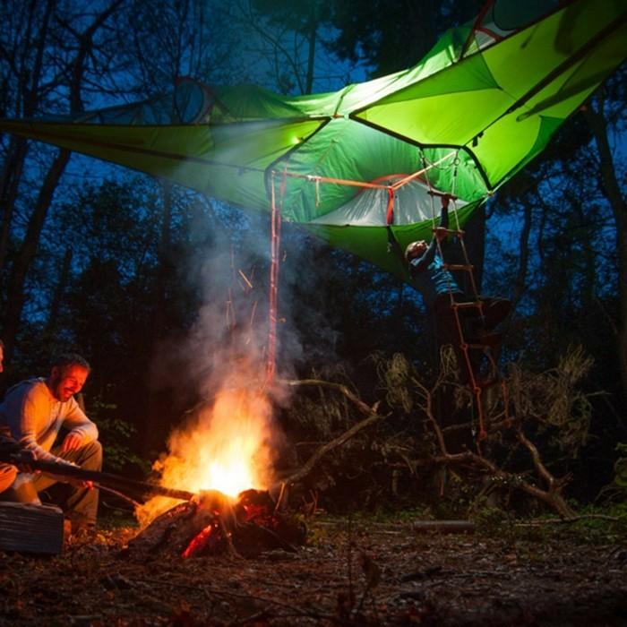 übernachten-in-dem-wilden-wald-ein-grünes-baumzelt-mit-strickleiter-und-ein-feuer