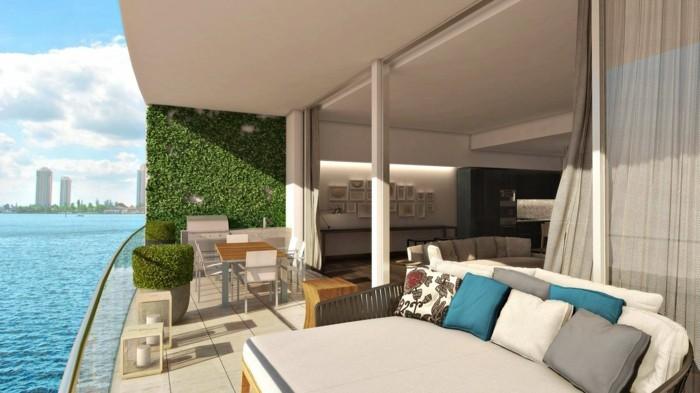 1-balkon-ideen-grüne-pflanzen-meer-tisch-stühle-kissen-großer-sofa-fliesen-modern