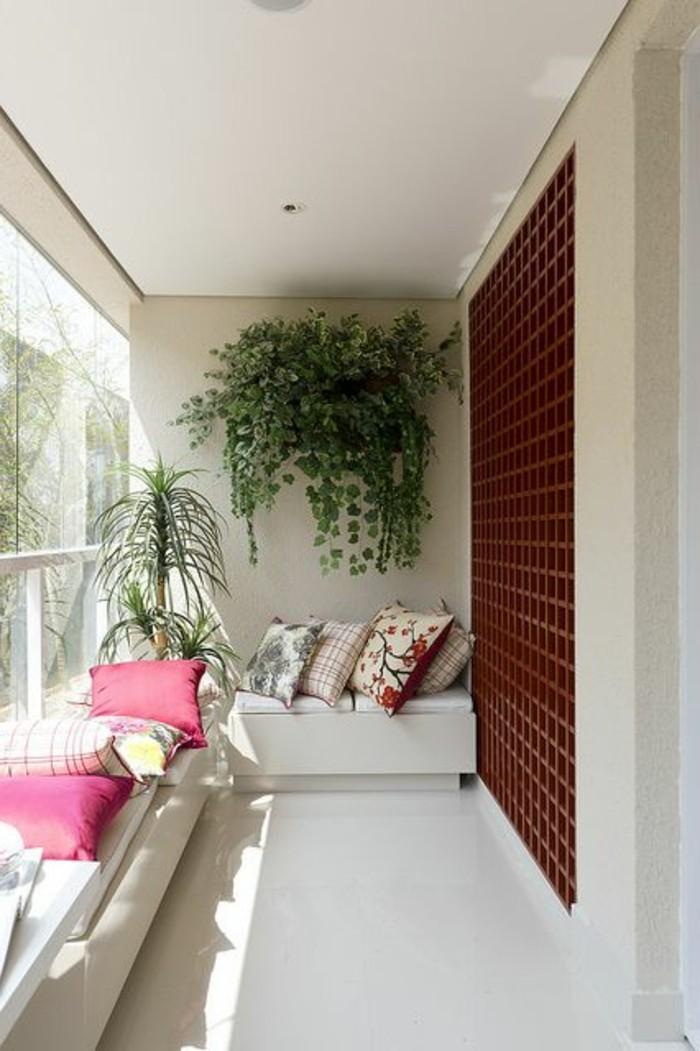 14-balkongestaltung-grüne-pflanzen-dekokissen-weißer-sofa-fliesen-fenster