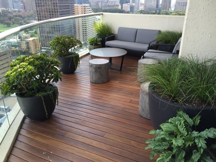 4-balkon-ideen-grauer-sofa-tisch-grüne-pflanzen-schwarze-blumentöpfe-boden-aus-holz-holzpaletten