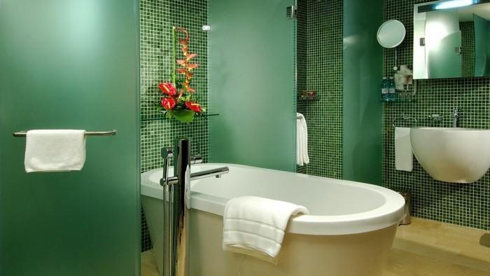Bäder-ohne-fliesen-mit-grünen-glaswänden-und-blumen-als-dekoration