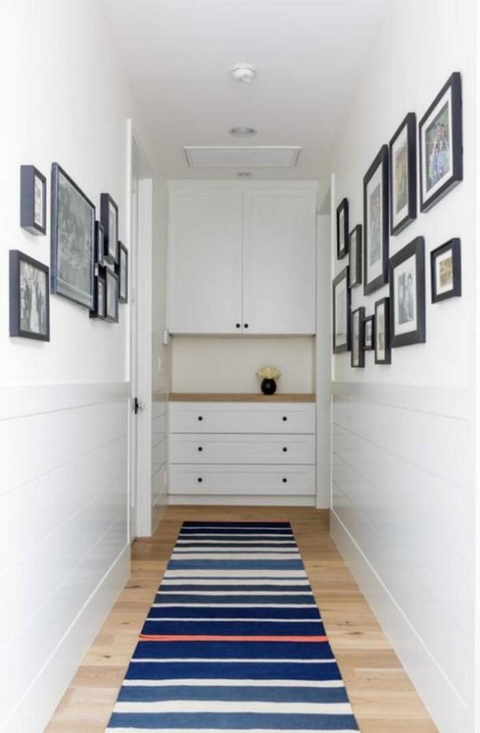 Langer-flur-deko-teppich-auf-streifen-und-bilder-an-den-wänden-regal-im-hintergrund