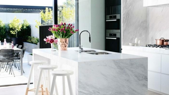 Wohnideen-küche-in-weiß-kücheninsel-weiße-stühle-blumen-waschbecken-fenster-ofen
