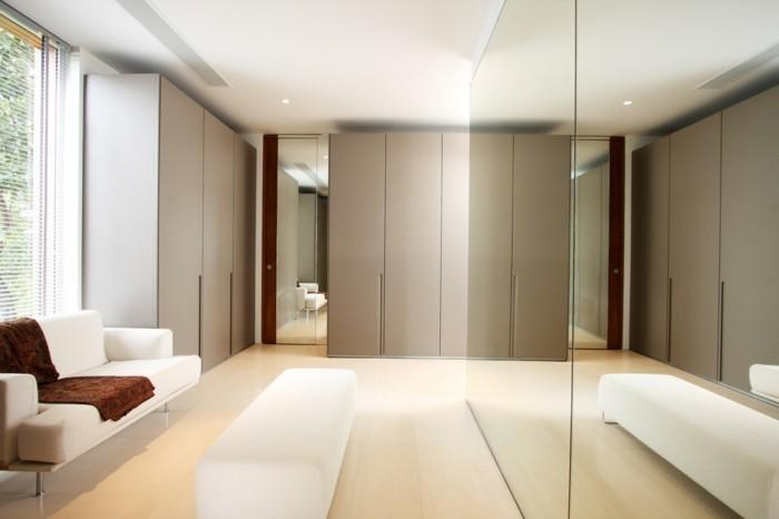 ankleidezimmer-ideen-sofa-schrank-hocker-in-dezenten-farben-im-grossen-begehbaren-schrank