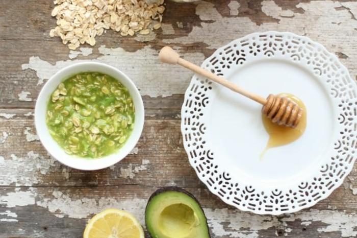 avocado-gesichtsmaske-weißer-teller-schale-zitrone-hölzerner-tisch-honig