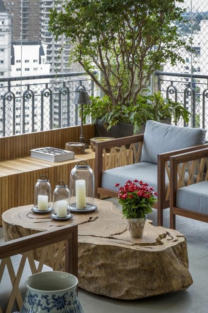 balkon-verschönern-blumen-tisch-aus-massivholz-weiße-kerzen-sessel-holz-baum-buch