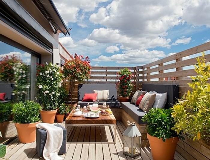 balkon-verschönern-boden-aus-holz-himmel-blumentöpfe-blumen-sofa-tisch