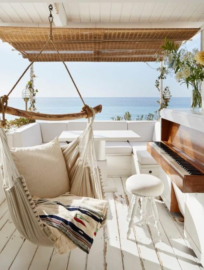 balkon-verschönern-boden-aus-holz-meer-hängematte-hocker-weiße-tisch-sofa