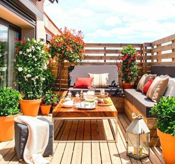 balkondekoration-orange-blumentöpfe-blumen-pflanzen-sofa-kissen-frühstück-hocker