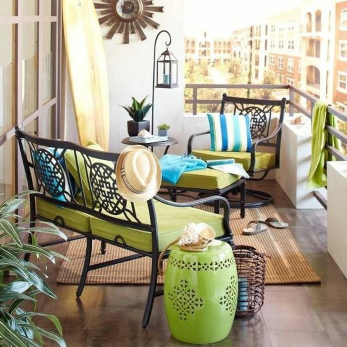 balkongestaltung-ideen-wanduhr-stühle-grüne-kissen-hocker-fliesen-tisch