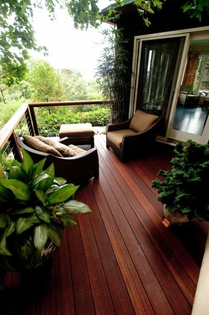 balkonideen-boden-aus-holz-sessel-hocker-grüne-pflanzen-fenster-bäume-kissen