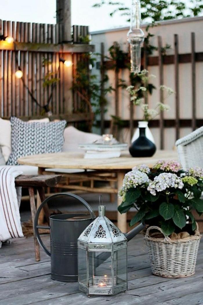 balkonideen-geflochtener-korm-windlicht-kerze-tisch-vasen-lampen-graue-gießkanne