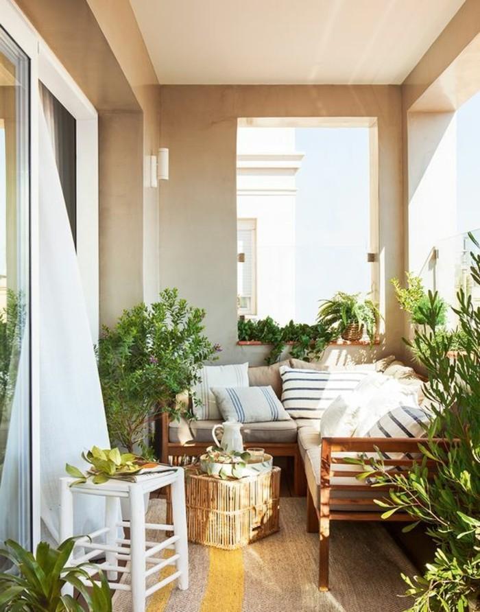 balkonideen-viele-grüne-pflanzen-sofa-kleiner-runder-tisch-weißer-hocker-gardinen