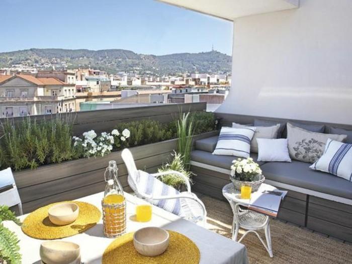 balkonideen-weißer-tisch-flasche-sofa-kissen-blumen-stühle-buch