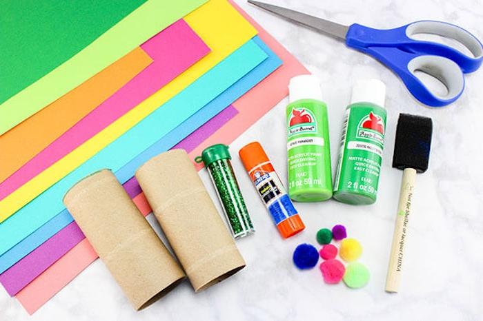 Materialien für DIY Frühlingsblumen, zwei Klorollen, Farben und Kleber, Glitzer und Bommeln, Schere und Papier