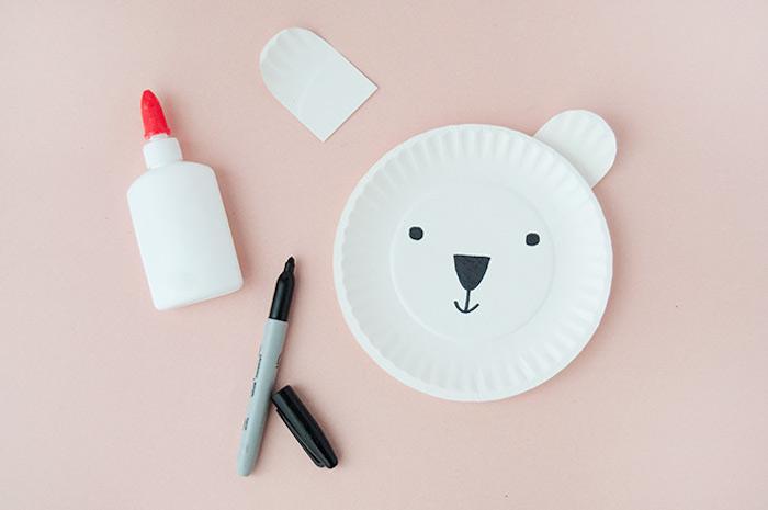 Eisbär basteln mit Pappteller, Gesicht mit schwarzem Filzstift malen