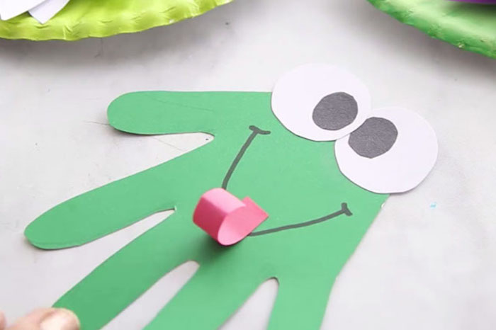 Handabdruck Frosch basteln, Augen und Zunge aus Papier schneiden