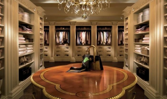 begehbarer-kleiderschrank-brauner-tisch-aus-massivholz-tasche-darauf-viele-regale-fuer-die-bekleidung