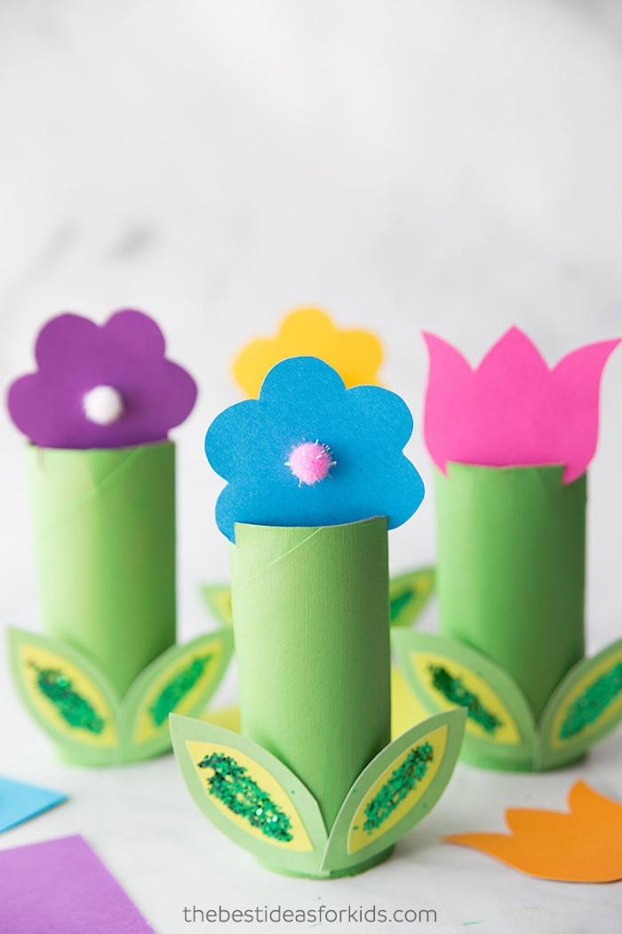 Frühlingsblumen basteln mit Klopapierrollen, Blüten aus Karton schneiden, kleine Bommeln kleben