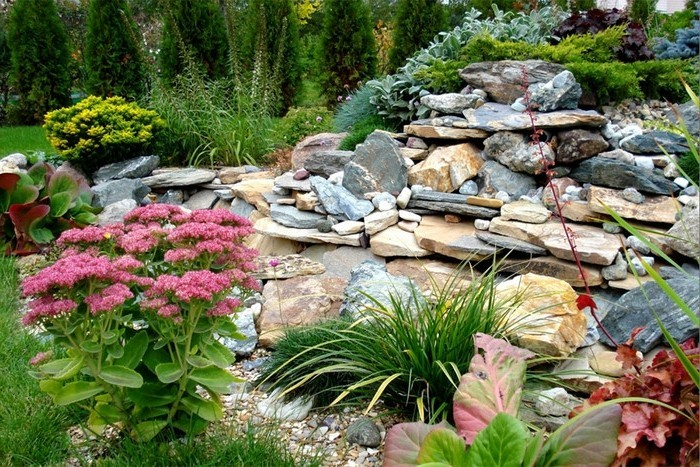 blumenbeet-mit-steinen-große-steine-kieferbäume-büschel