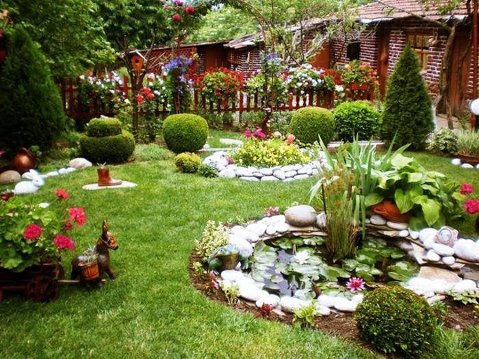 blumenbeet-mit-steinen-verschieden-pflanzen-dekorativer-pferdewagen-holzzaun-büsche-kieferbäume
