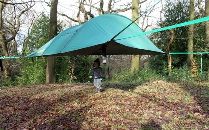 ein-grünes-campingzelt-im-wald-und-ein-kind